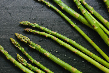 Fresh picked asparagus spears on black slate countertop