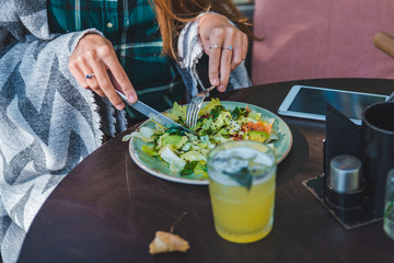 woman in cafe eating salad hands close up no face