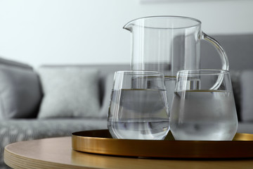 Tray with jug and glasses of water on table in room, space for text. Refreshing drink
