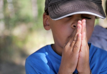 boy praying to God stock image with hands held together with closed eyes and white background stock photo