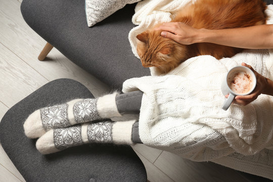 Woman with cute red cat and coffee on grey sofa at home, top view