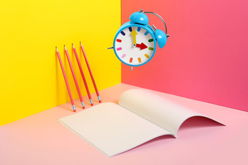 Alarm clock and empty book pages on color background. Mockup for design