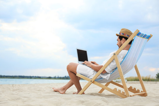 Young man with laptop sitting in deck chair on sea beach. Space for text