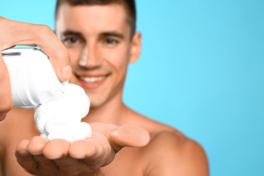 Handsome young man with shaving cream on light blue background, closeup view. Space for text