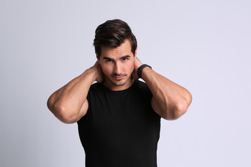 Portrait of handsome young man in black t-shirt on grey background