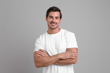Portrait of handsome young man in white t-shirt on grey background