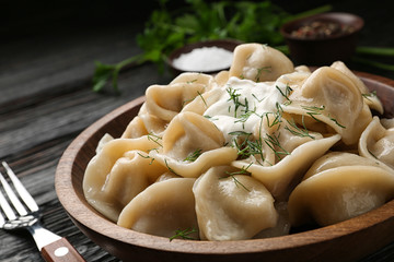 Tasty dumplings with sour cream in bowl on black wooden table, closeup