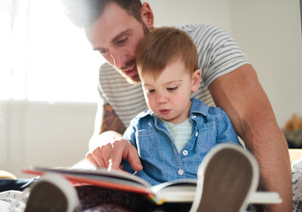 Adorable, young female toddler learning to read book with handsome millennial father on bed