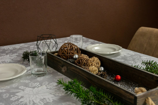 Christmas dining table with a lot of decoration. conifer branches, glitter, random figures and more.