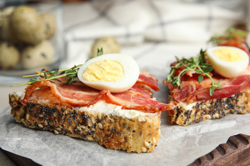 Cutting board of delicious bruschettas with prosciutto on table, closeup