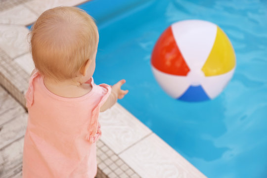 Little baby reaching for inflatable ball at outdoor swimming pool. Dangerous situation