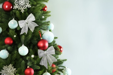 Fotobehang - Beautiful Christmas tree with decor against light grey background. Space for text