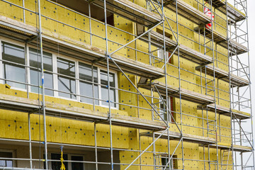 Obraz scaffolding arround the house to install thermal insulation of the apartment building facade - fototapety do salonu