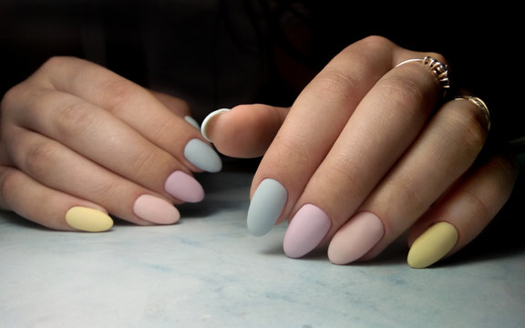 Colorful manicure with multi-colored coating. Long round nails with color matte design.