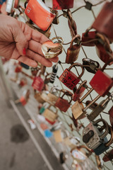 Close up of hand holding love padlock railing