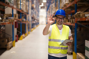 Successful goods distribution and warehouse organization. Warehouse worker standing in large storage center and showing OK hand gesture satisfied on delivering goods.