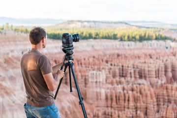 Man taking pictures of view from Bryce Point overlook of hoodoos rock formations in Bryce Canyon National Park at sunset with tripod and camera
