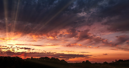 Dramatic Sunset over Storm Clouds. Evening, Large beautiful orange color sunset sky. Red purple orange blue pink. Landscape of Storm clouds moving across the sky against the setting sun.