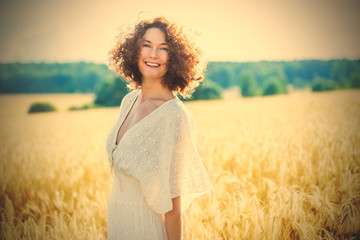 beautiful woman in a white dress in a wheat field