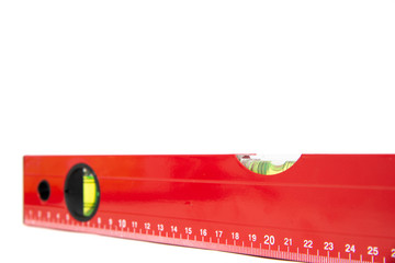 Red spirit level isolated on a white background. The concept of building a house, doing home renovations. Getting the right level, attention to detail.