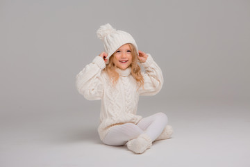 Winter clothes. Portrait of a little curly-haired girl in a knitted white winter hat. little blonde girl in white knitted hat and sweater smiling light background isolate, space for text