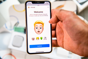 PARIS, FRANCE - SEP 24, 2018: Unboxing of iPhone Xs Max with demonstration of Messaging App with new Animoji Memoji features characters - augmented reality communication create own blonde hair man