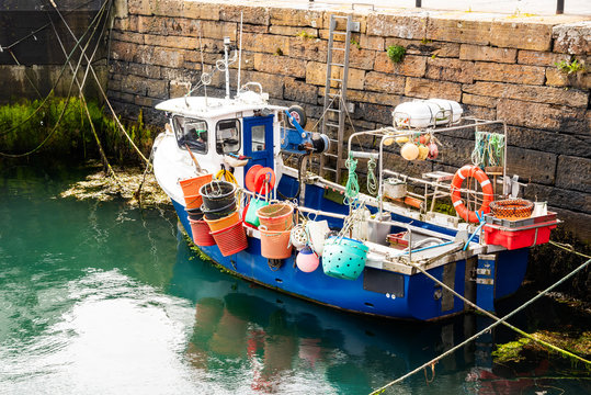 Small fishing boat full of colourful buckets and buoys moored in a harbor