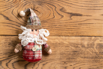 Christmas decoration and Santa Claus rag doll on wooden background