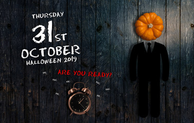 Date of Halloween 2019 with alarm clock on wooden background