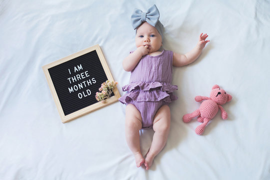 Shot from overhead of three months old baby girl laying down on white background with letter board and teddy bear.