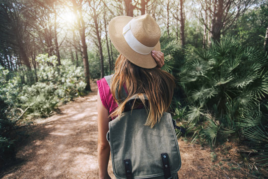 Hipster tourist girl walking through the jungle forest