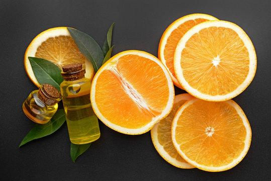 Composition with orange essential oil on dark background