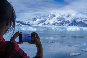 Woman is wearing a lumberjack shirt and taking a picture of Hubbard Glacier on her mobile phone. This is beautiful Alaska and you can see it on the screen of smartphone. Snowy mountains and iceberg.