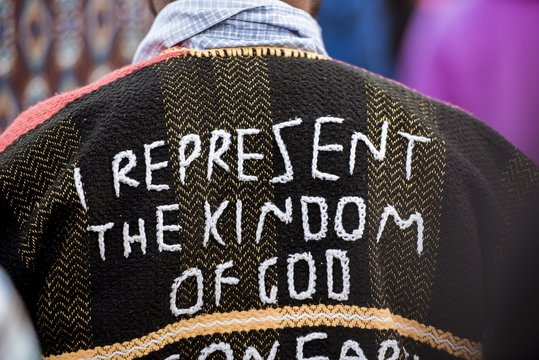 """Closeup shot of a person's back wearing a coat with """"I represent the kingdom of God"""" sewn on it"""