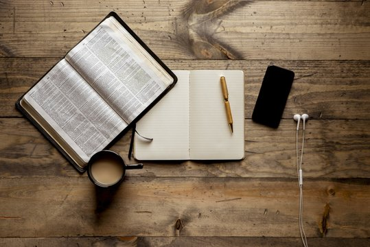 Overhead shot of a notebook with a fountain pen near an open book and smartphone on wooden table
