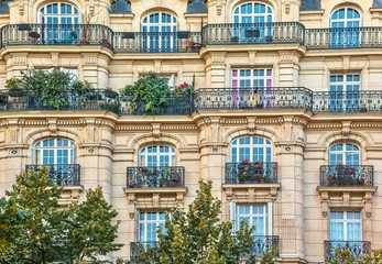 Street view of an old, elegant residential building facade in Paris, with ornate details in the stone walls, french doors and wrought iron railings on the balconies. Wall mural
