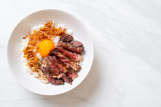 sliced beef on topped rice bowl with egg