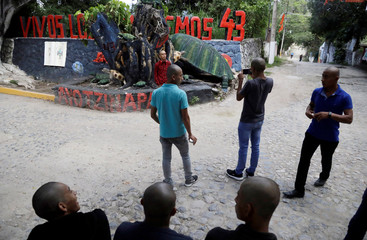 """Teacher trainees take pictures of a monument in memory of the missing students of the Ayotzinapa Teachers Training College """"Raul Isidro Burgos"""" in Tixtla"""