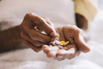pills in a Senior's hands. Painful old age. Caring for the health of the elderly