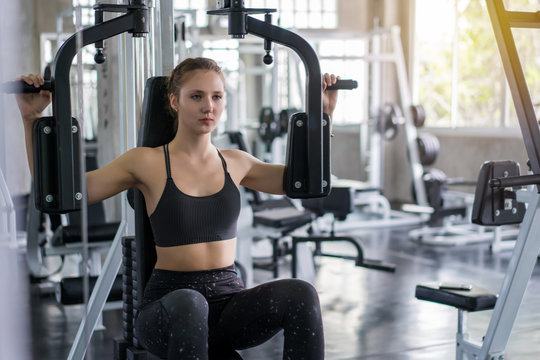 Young woman lowering weight of fitness machine and working out in the fitness gym