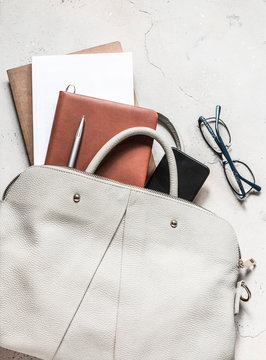 Women's bag with office accessories on a light background, top view