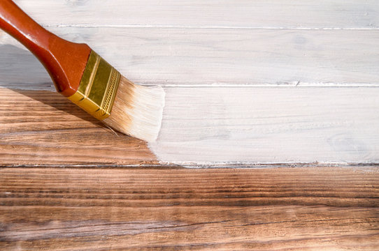 painting brush covers the wood textured floor with white paint