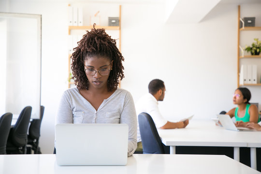 Serious excited African American employee working on computer in office. Her colleagues talking at meeting table in background. Workgroup in office concept