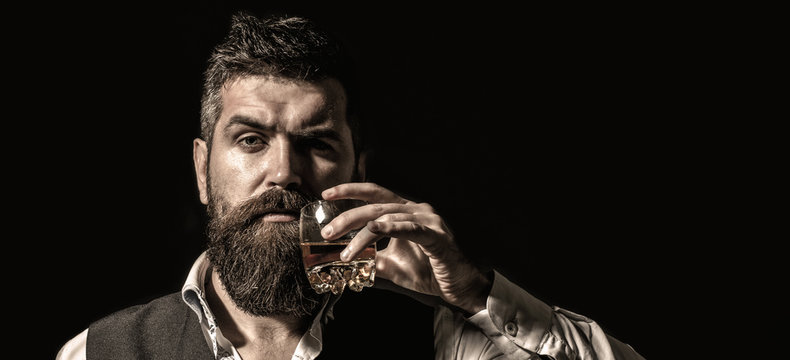 Rich man with a holding glass whiskey. Attractive man with a whiskey. Stylish handsome male in suit drink from glass brandy, cognac. Portrait of a handsome bearded in elegant tuxedo, drink cognac.