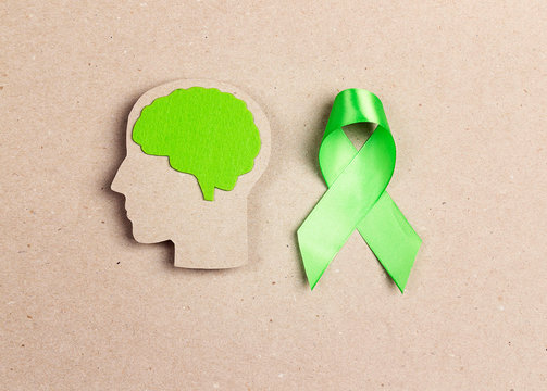 World mental health day concept. Green awareness ribbon and brain symbol.