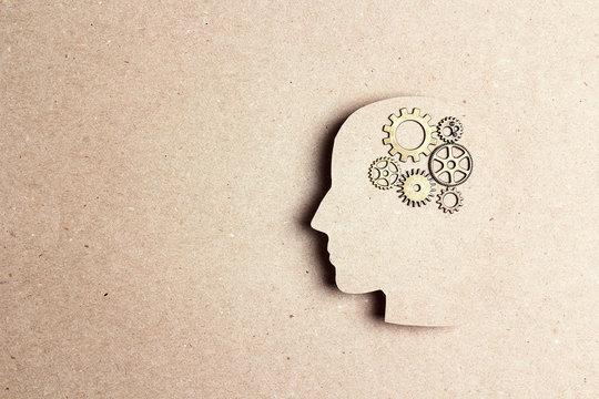 Silhouette human head with gears wheels.