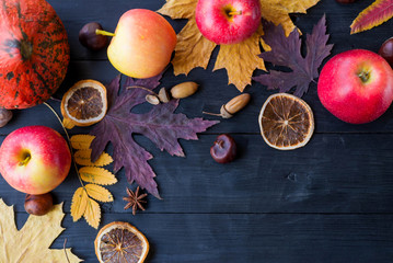 Autumn composition with copy space: yellow leaves, apples, pumpkin on a wooden table.