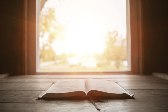 Close shot of holy bible on a wooden surface with the sun shining in the background