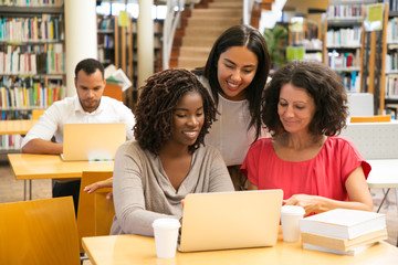 Smiling students working with laptop at library. Mature women working at public library. Education...