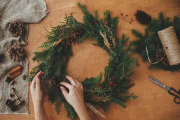 Hands holding christmas wreath with fir branches, berries, pine cones, and thread, scissors on rural wooden table. Rustic Christmas wreath, flat lay. Christmas wreath workshop